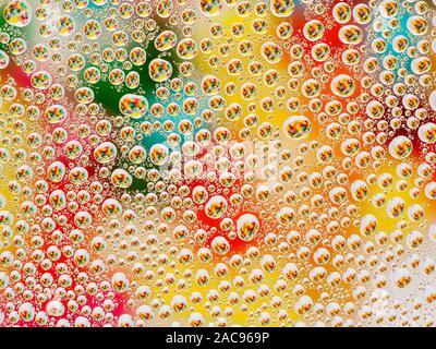 Abstrakte bunte lebendige Hintergrund mit großen und kleinen sphärischen konvexen Tropfen Wasser auf das Glas. Makro, Ansicht von oben, aus der Nähe. - Stockfoto