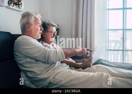 Fröhlich glücklich Schöne kaukasischen Alten senior Paar hinsetzen und entspannen auf der SOA zu Hause schauen und über einen Computer laptop zu genießen - Stockfoto