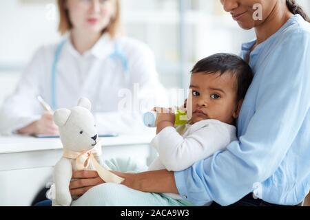 Portrait von baby boy liegen auf Mutters Knie und Suchen an der Kamera, während Sie besuchen Arzt am Krankenhaus - Stockfoto