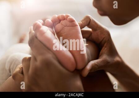 Close up Portrait von afroamerikanischen Frau mit winzigen Füßen von niedlichen Baby im Sonnenlicht, kopieren Raum Stockfoto