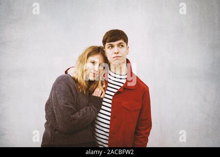 Junge zärtlich Paar stand vor der Beton Zement Wand mit Kopie Raum - Stockfoto