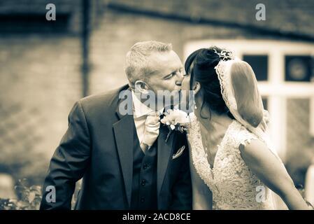Ein Brautpaar küsst sich an ihrem großen Tag und feiert gemeinsam Liebe und Glück und ihre Zukunft - Stockfoto