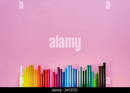 Spektrale Sequenz von Farbstiften auf rosa Hintergrund. Nahaufnahme, flach hinlegen