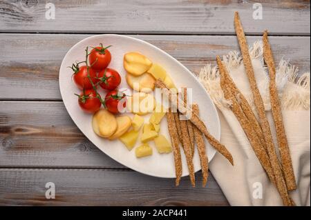 Traditionelle italienische Gerichte grissini Brot mit Schinken, Käse und Tomaten mit Kräutern auf einem Schild auf einem hölzernen Hintergrund. Gesund Stil. Kopieren - Stockfoto