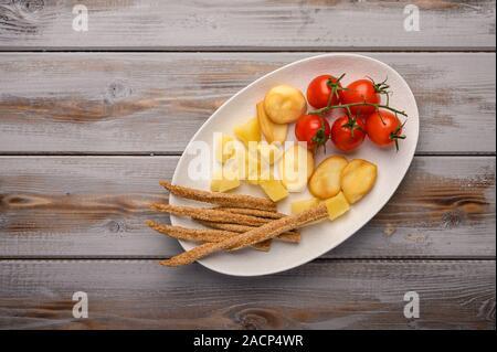 Traditionelle italienische Gerichte grissini Brot mit Schinken, Käse und Tomaten mit Kräutern auf einem Schild auf einem dwooden Hintergrund. Gesund Stil. Kopieren - Stockfoto