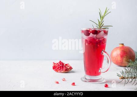 Granatapfel Weihnachten Cocktail mit Rosmarin, Champagner, club Soda auf grauem Beton Tabelle. Close Up. - Stockfoto