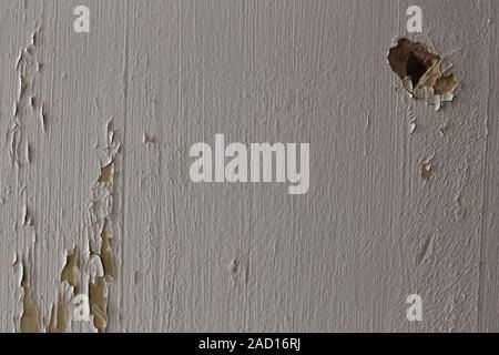 Risse an der Wand mit weißer Farbe und eine Bohrung - Stockfoto