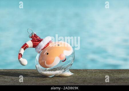 Weihnachten in Florida Konzept. Santa Ornament mit hellen blauen See Hintergrund in Orlando, Florida. - Stockfoto