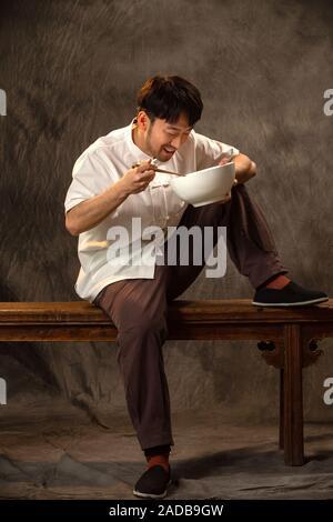 Der junge Mann sitzen zu essen - Stockfoto