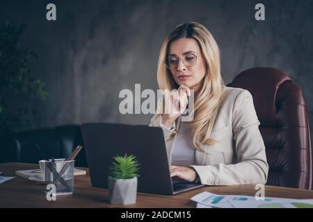 Foto von Konzentriertem zuversichtlich Smart clever lady Lösung buciness Problem sitzen am Tisch mit Netbook - Stockfoto