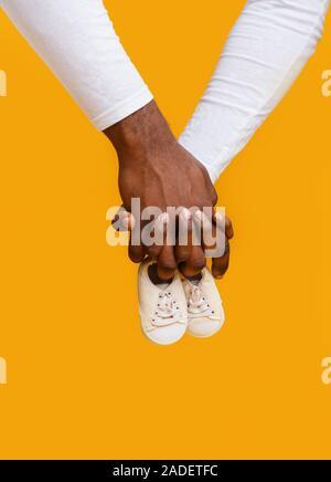 Hände von schwarz Paar hält Baby Stiefel zusammen Stockfoto