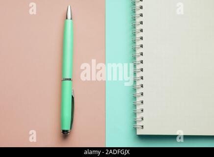 Spirale Notebook mit leeren Seiten und Füllfederhalter auf Pastell rosa und Mint Hintergrund, Ansicht von oben, flach - Stockfoto