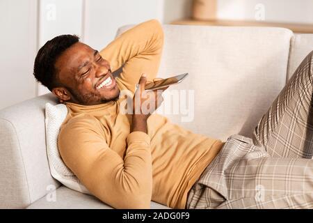 Mann mit Phone Voice Assistant liegen auf der Couch zu Hause - Stockfoto