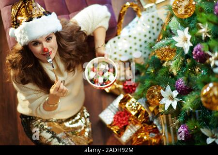 Obere Ansicht von Happy moderne Frau mit langen brünetten Haar in Gold Pailletten Rock und weißen Pullover mit gesunden Salat, rote Nase mit Cherry Tomaten - Stockfoto