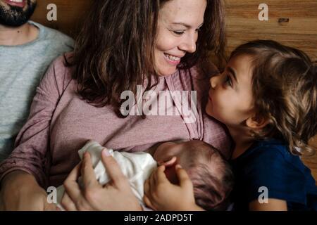 Mom lächelt junge Tochter beim Stillen neugeborenes Baby - Stockfoto