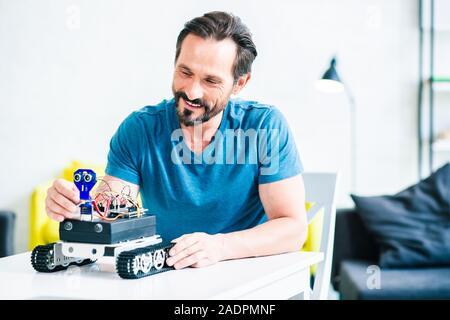 Fröhliche bärtiger Mann seine Roboter zu Hause - Stockfoto