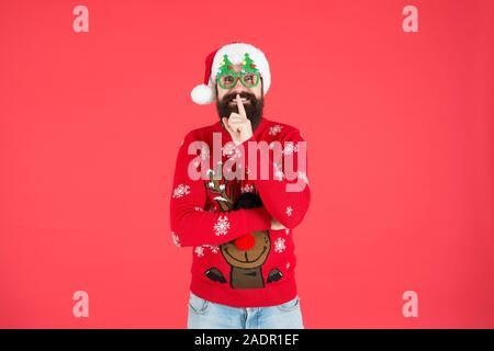 Geheim zu halten. Frohes neues Jahr feier. Melden Sie Urlaub Feier. Winter party Outfit. Pullover mit Rotwild. Hipster bärtiger Mann tragen Winterkleidung roten Hintergrund. Weihnachtsfeier Ideen. - Stockfoto