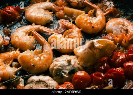 Garnelen gebraten in der Pfanne mit Knoblauch und Tomaten - Stockfoto
