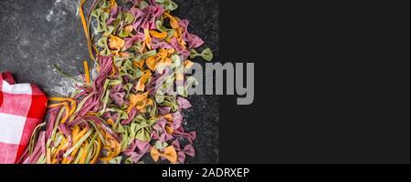Vielzahl an raw Nudeln, farfalle Bow-tie, Fettuccine oder Tagliatelle bunte Nudeln auf grauem Hintergrund mit Mehl Stockfoto