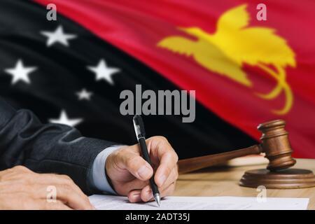 Richter schreiben auf Papier im Gerichtssaal mit Papua Neu Guinea Flagge Hintergrund. Holz- Hammer der Gleichstellung Thema und rechtlicher Begriff. - Stockfoto