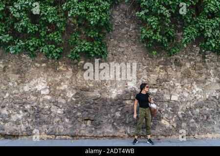 Aktive junge Frau mit ihrer Tasche hängen, neben einer Steinmauer suchen Stockfoto