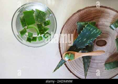 Aloe Vera Blätter auf einem Bambus Löffel und in ein Glas mit Wasser auf einem weißen Hintergrund. Medizin und Pflege. - Stockfoto