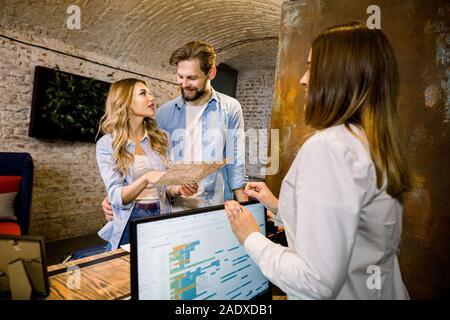 Rezeptionistin, touristische Informationen, glückliches junges Paar, halten Sie den Stadtplan, stehend an der Rezeption - Stockfoto