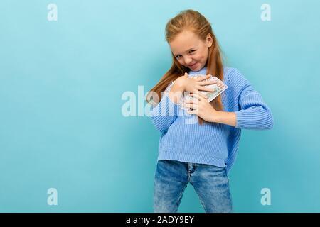Attraktive europäische Mädchen, dass Geld in den Händen auf einem hellblauen Hintergrund. - Stockfoto