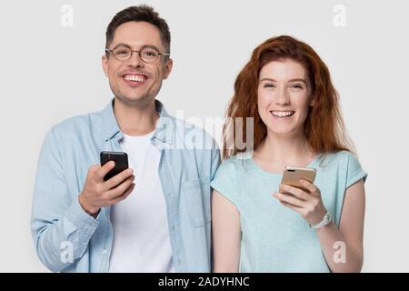 Happy tausendjährigen Familie Paar hält Smartphones. - Stockfoto
