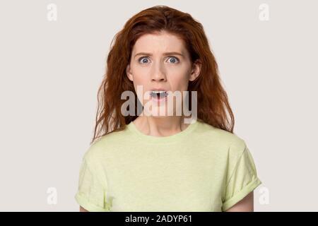 Studio Portrait negativ überrascht junge rothaarige Frau. - Stockfoto