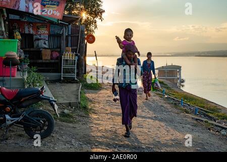 Eine burmesische 3-köpfige Familie (Mann, Frau und Kind auf den Schultern) nach Hause laufen nach dem Einkaufen entlang der Chindwin Fluss im Nordwesten Myanmar (Birma) - Stockfoto
