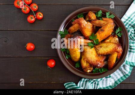 Gebackene Chicken Teriyaki Flügel in Honig Senf Sauce auf dunklen Holztisch. Asiatische Rezept. Im rustikalen Stil. Ansicht von oben. Flach. - Stockfoto