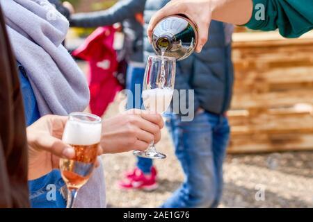 Gerne Freunde gießen Champagner Sekt in Gläser im Freien. Das Konzept der ein Picknick. - Stockfoto