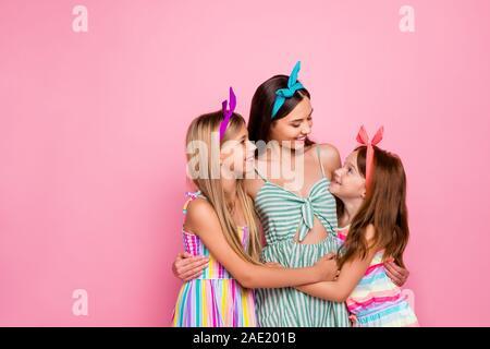 Portrait von süßen Schwestern umarmen suchen tragen helles Kleid rock Stirnbänder über rosa Hintergrund isoliert - Stockfoto