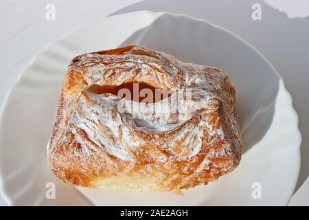 Frisch gebackenen Blätterteig mit Hüttenkäse. Europäisches Frühstück. Backen auf einer weißen Platte. - Stockfoto