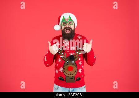 Total gut. Frohes neues Jahr feier. Melden Sie Urlaub Feier. Winter party Outfit. Pullover mit Rotwild. Hipster bärtiger Mann tragen Winterkleidung roten Hintergrund. Weihnachtsfeier Ideen. - Stockfoto