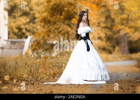 Frau in einem weißen viktorianischen Kleid in einem Herbst Park Stockfoto