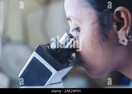 Nahaufnahme von Frau mit einem Mikroskop im Labor-Wissenschaftlerin beschäftigt sich mit Mikroskop. - Stockfoto