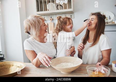 Mehl auf der Nase. Mutter, Großmutter und Tochter eine gute Zeit in der Küche Stockfoto