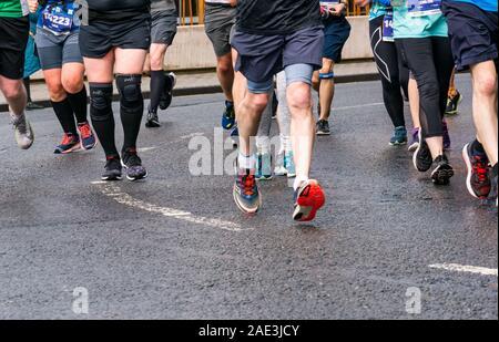 Close up Läufern Beine, Füße und Schuhe auf nassem Asphalt Road, Edinburgh Marathon Festival 2019, Schottland, Großbritannien - Stockfoto