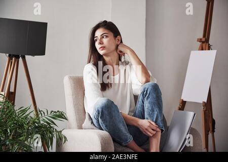 Entspannt Frau sitzt auf dem Stuhl und uns auf die Seite. Junge Brünette im Zimmer mit weißen Wänden und Tageslicht, die sich aus dem Fenster