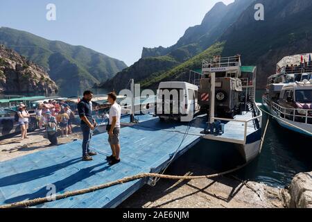Koman, Albanien, dem 7. Juli 2019: Fähre ist geladen mit Autos und Passagiere in Koman, Komani See, ein 35 km langer Stausee in den Dinarischen Alpen - Stockfoto