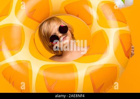 Porträt eines hübschen Europäischen blonde Junge im gelben Badehose und Sonnenbrille mit einem Kreis Ananas auf orangem Hintergrund. - Stockfoto