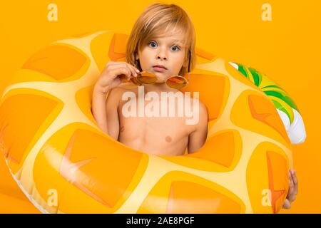 Portrait von hübschen Europäischen blonde Junge im gelben Badehose und Sonnenbrille mit einer Ananas fadenscheinigen schwimmen Kreis auf eine Orange Studio Hintergrund. - Stockfoto