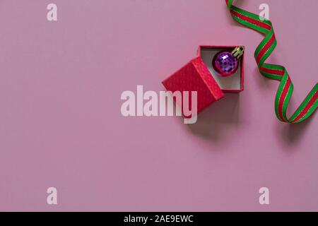 Rot Geschenk oder präsent, und lila Weihnachten bubble Öffnen innen mit rot grün Ribbon auf rosa Tabelle Ansicht von oben. Flach. Geburtstag, Hochzeit oder Weihnachten - Stockfoto