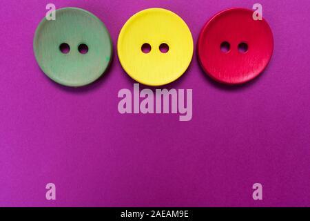 Drei große mehrfarbige Tasten auf einem rosa Hintergrund. Kopieren Sie Platz. - Stockfoto