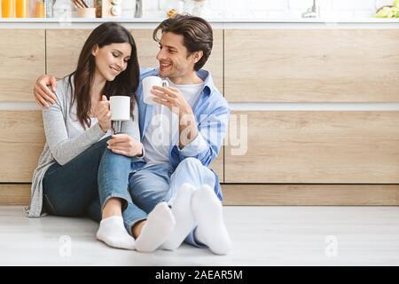 Happy tausendjährigen Paar ruht auf Küche Etage mit Hot Cups - Stockfoto