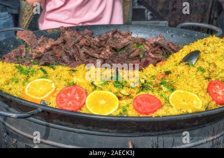 Große paella Pfanne mit separaten Fleisch, im Außenbereich gekocht. Eine der Mahlzeiten, mit Reis, die meisten berühmten in Spanien. Schönen Kontrast der intensiven Farbe - Stockfoto