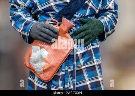 Eine anfällige Rentner im Morgenmantel und woollen Handschuhe mit einem hot-eater Flasche mit Gaffer-tape gepatcht, die versuchen, warm zu halten als Heizkosten steigen - Stockfoto