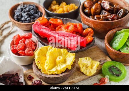 Vielzahl von getrockneten Früchten in Schalen. Datteln, Rosinen, getrocknete Aprikosen und exotische Getrocknete Ananas, Papaya und Kiwi, weisser Hintergrund. - Stockfoto